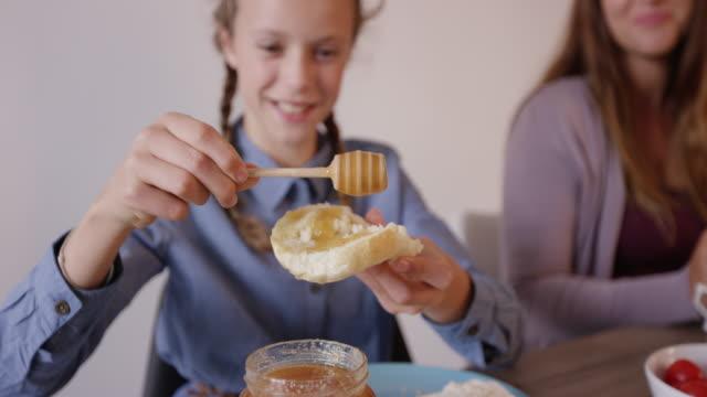 女子高生の笑顔とパンに蜂蜜を置く - 食パン点の映像素材/bロール