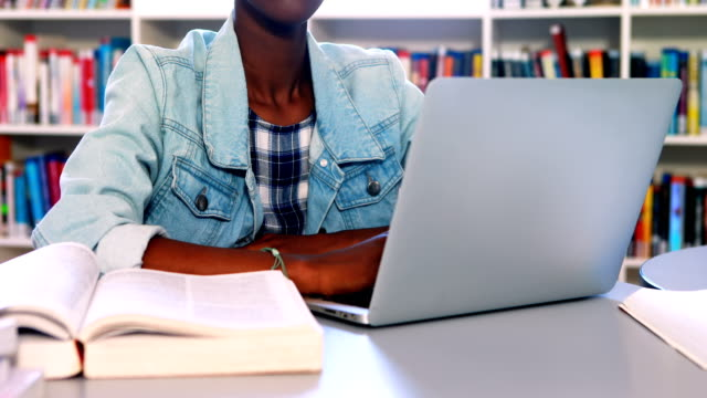 School girl using laptop in library video