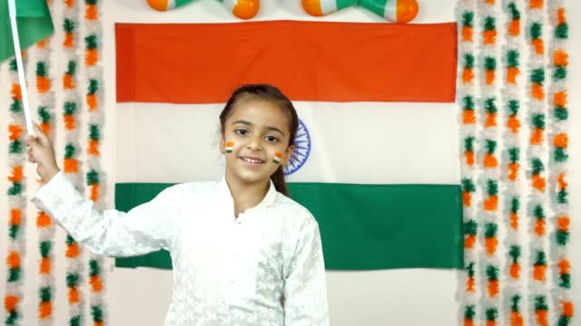 okul küçük hint kız hindistan bayrağı sallayarak gidiyor-bağımsızlık günü veya cumhuriyet günü kavramı - orta plan plan türleri stok videoları ve detay görüntü çekimi