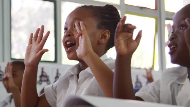 Crianças de escola, contando com os dedos numa escola primária - vídeo