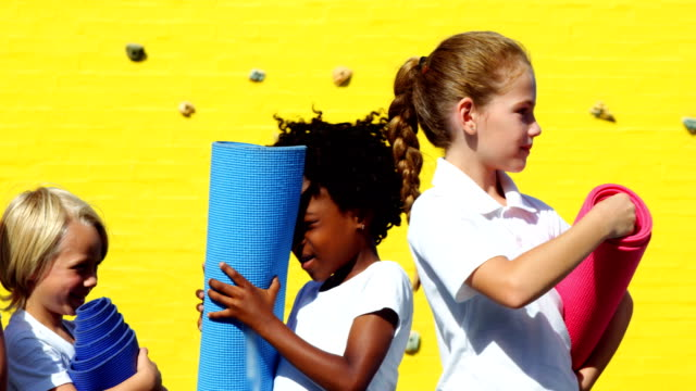 School Kids Holding Yoga Mat And Interacting With Each Other