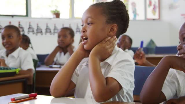 okul çocukları bir ilköğretim okulunda ders sırasında dinleme - okul çocukları stok videoları ve detay görüntü çekimi