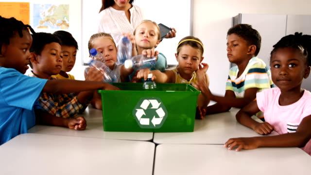 School kids putting waste bottles in recycle bin in classroom video