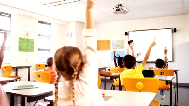 School kids raising hand in classroom School kids raising hand while teacher teaching in classroom at school elementary age stock videos & royalty-free footage