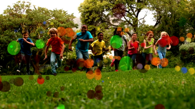 School kids running in slow motion towards the camera in a park