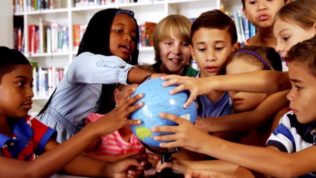 scuola bambini in biblioteca studiando mondo - geografia fisica video stock e b–roll