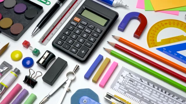 school office stationery supplies flat-lay on white table background top view. - school supplies stock videos and b-roll footage