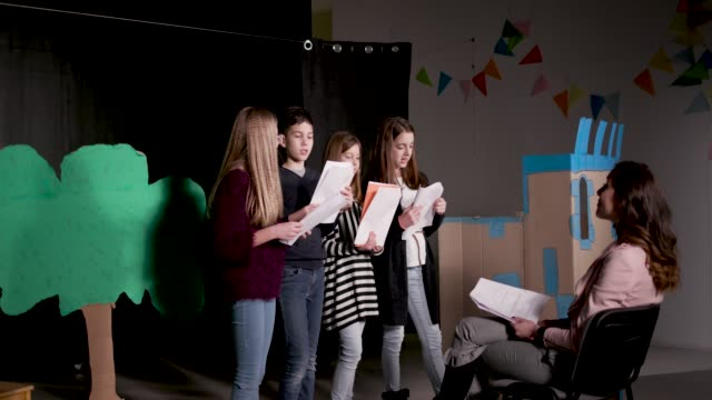 School Play Rehearsal Group of children enjoying drama club rehearsal. They are reading script with their drama teacher. performing arts event stock videos & royalty-free footage