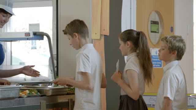 school pupils being served lunch in canteen shot on r3d - stołówka filmów i materiałów b-roll
