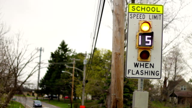 A school speed limit when flashing - fifteen miles an hour sign - close up angle A school speed limit when flashing - fifteen miles an hour sign - close up angle time zone stock videos & royalty-free footage