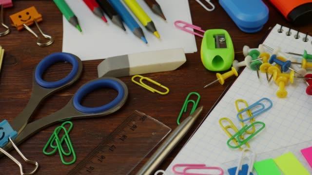 vidéos et rushes de papeterie d'école sur la table en bois brune - fournitures scolaires