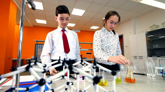 School students working on a chemistry project together in chemistry classroom. School students working on a chemistry project together in chemistry classroom. 4K. group of objects stock videos & royalty-free footage