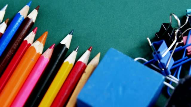 School supplies arranged on green background video