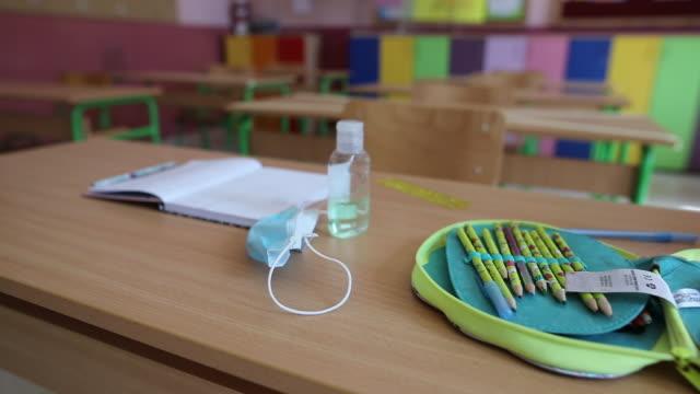 przybory szkolne, maska na twarz i dezynfekcji rąk na biurku w klasie szkoły podstawowej - przybory szkolne filmów i materiałów b-roll