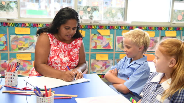 School teacher writing in boy's book and then handing it back to him video