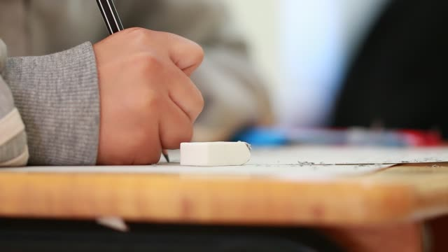 scuola/università gli studenti fanno gli esami, scrivono la sala d'esame con matita in possesso su modulo ottico risponde foglio di carta sulla scrivania facendo il test finale in classe. concetto di valutazione dell'istruzione - esame università video stock e b–roll