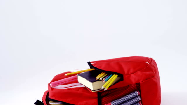 Schoolbag with various supplies on white background video