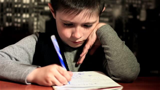 Alumno realiza diligentemente sus deberes en la mesa. Cierre para arriba - vídeo