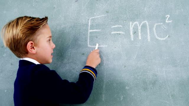 Schoolboy doing maths on chalkboard video