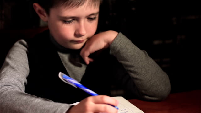 Niño dibuja dibujos en su cuaderno de notas en lugar de sus tareas - vídeo