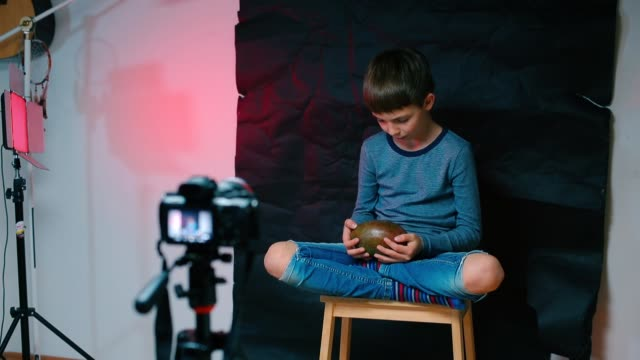 A schoolboy is doing a video blog.