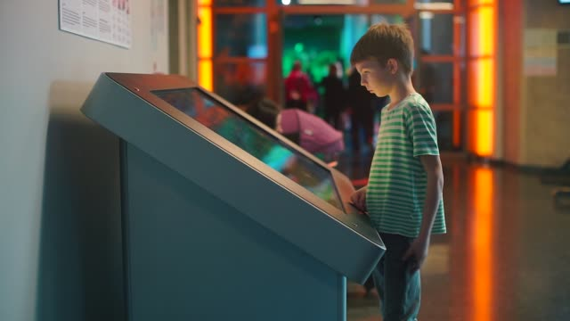 A schoolboy is standing in front of a large touch screen.