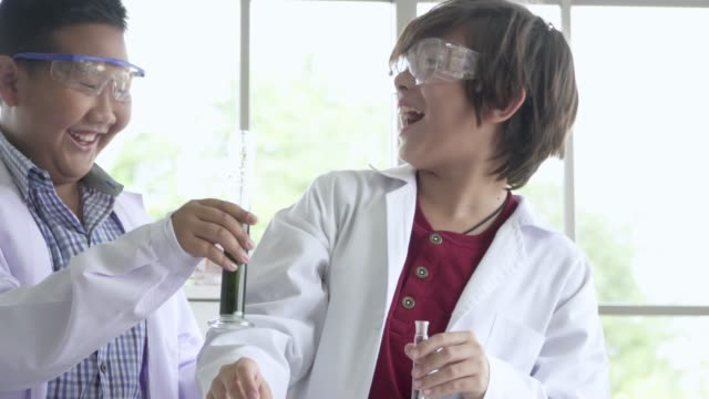Schoolboy pipetting samples into small flask with his lab partner