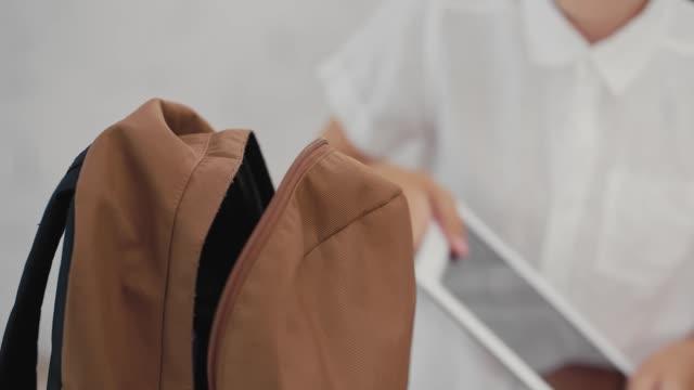 vídeos de stock e filmes b-roll de schoolboy puts a tablet computer in a backpack. back to school. - mochila saco