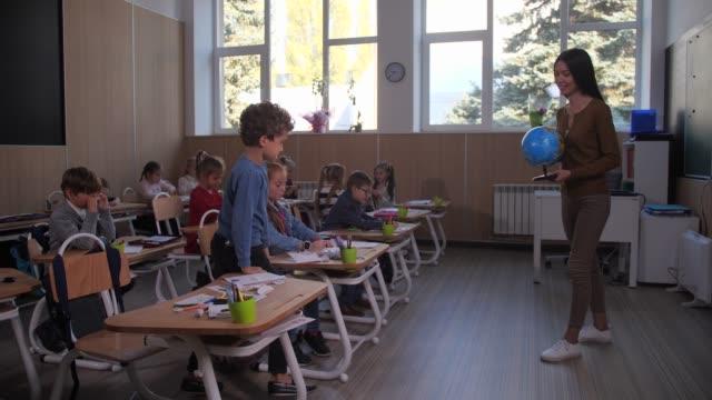 scolaro che alza la mano durante la lezione di geografia - geografia fisica video stock e b–roll