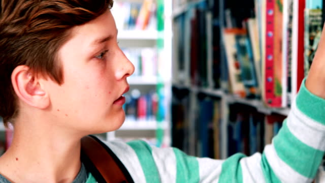 Schoolboy selecting book in library video