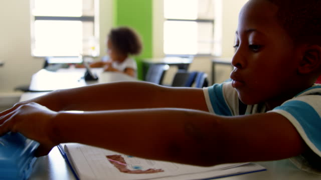 Schoolboy sitting at desk and studying in classroom 4k