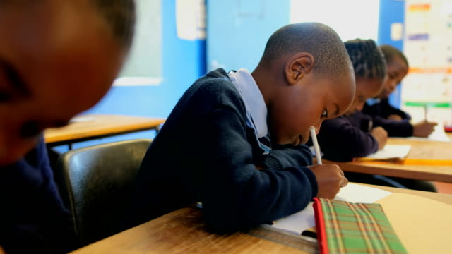 Schoolboy studying in the classroom at school 4k Thoughtful schoolboy studying in the classroom at school 4k school building stock videos & royalty-free footage