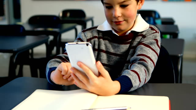 Schoolboy using mobile phone in classroom 4k video