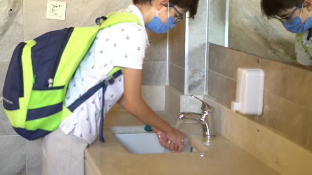 stockvideo's en b-roll-footage met schooljongen die beschermend medisch masker en het wassen van handen draagt. - schooljongen