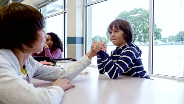 vídeos y material grabado en eventos de stock de schoolboys brazo luchan durante el almuerzo en la cafetería de la escuela - escuela media