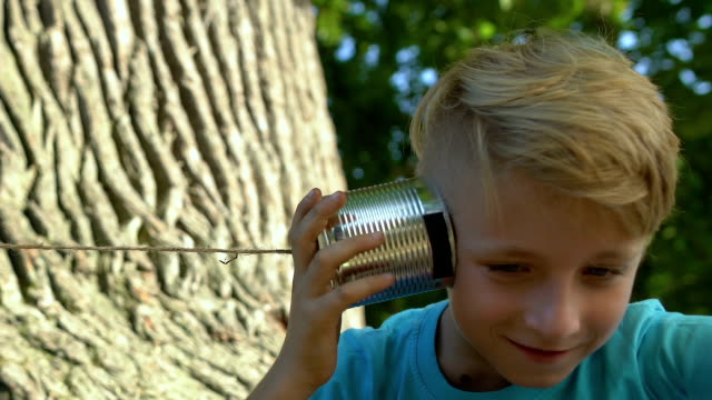 schoolboys communicating through can telephone, children having fun together - scolaro video stock e b–roll