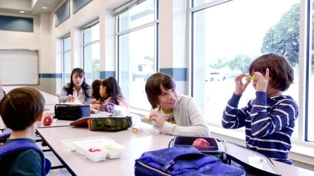 stockvideo's en b-roll-footage met school jongens genieten van een lunch samen in de school cafetaria - schoolkinderen