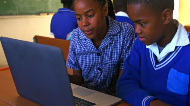 stockvideo's en b-roll-footage met schoolkinderen die laptop gebruiken in een les op een township school 4k - schooljongen