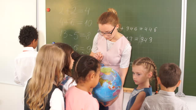 vídeos de stock e filmes b-roll de schoolchilds looking at globe with teacher at geography lesson - teacher school solo