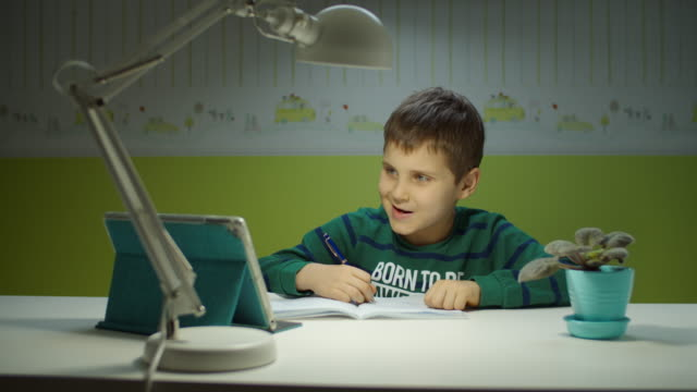 schooler boy making online homework with tablet computer. kid sitting at the desk and studying online in children room at home. - 8 9 anni video stock e b–roll