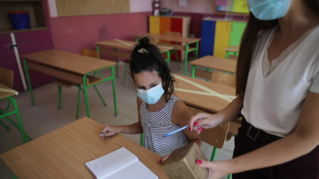 Schoolgirl and teacher on math class at classroom of elementary school during covid-19 pandemic
