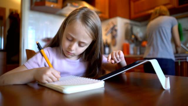 skolflicka surfa på hennes tablett hemma och skriva ner i en anteckningsbok - enföräldersfamilj bildbanksvideor och videomaterial från bakom kulisserna