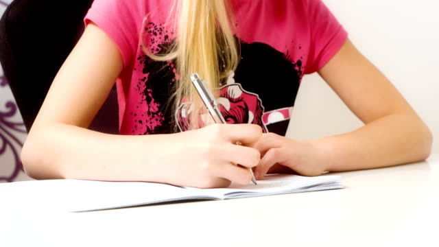 schoolgirl doing homework at home - çalışma kitabı stok videoları ve detay görüntü çekimi