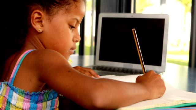 schoolgirl doing homework in library 4k - 8 9 anni video stock e b–roll