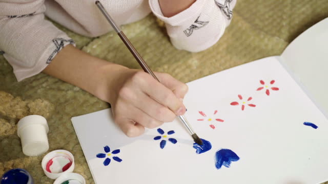 Schoolgirl drawing with gouache greeting card with flowers for her mother video