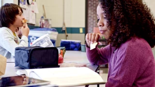 Schoolgirl eats lunch alone in school cafeteria