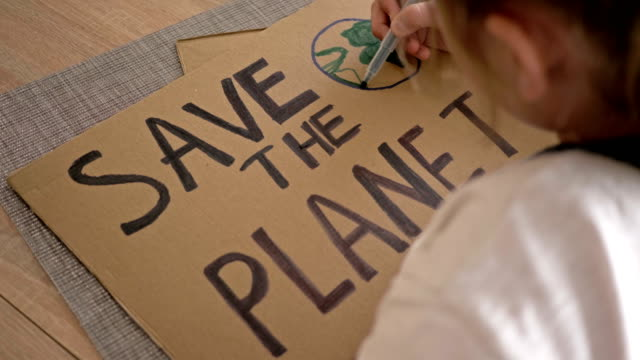 schoolgirl makes a poster save the planet - clima video stock e b–roll