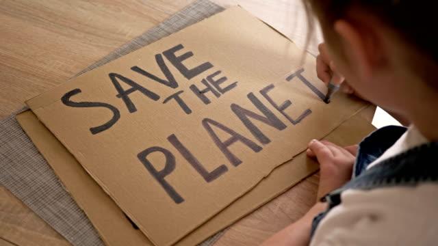 vídeos de stock e filmes b-roll de schoolgirl makes a poster save the planet - green world