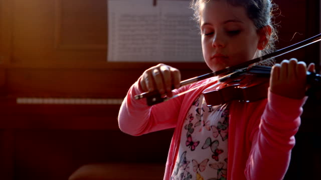 Schoolgirl playing violin in music class 4k video