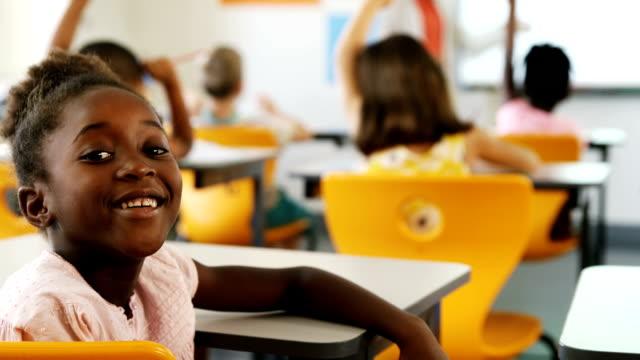 Schoolgirl raising hand in classroom video